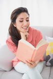 Cheerful brunette sitting on her sofa reading a book Stock Photos