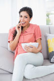 Cheerful brunette sitting on her sofa watching tv eating bowl of popcorn Royalty Free Stock Photo