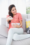 Cheerful brunette sitting on her sofa watching tv holding bowl of popcorn Royalty Free Stock Images