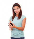 Cheerful brunette texting and smiling at you Royalty Free Stock Photos