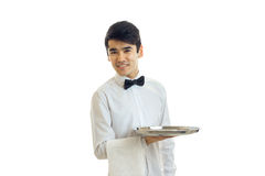 Cheerful brunette waiter man with silver tray in hands smiling. Isolated on white background stock images