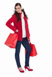 Cheerful brunette in winter clothes posing and holding shopping bags Stock Images