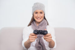 Cheerful brunette with winter hat on playing video games Stock Photography