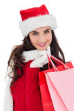 Cheerful brunette in winter wear holding shopping bags Stock Image