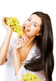 Cheerful brunette woman eating grape Royalty Free Stock Photos