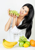 Cheerful brunette woman with green grape Royalty Free Stock Photo