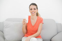 Cheerful brunette woman holding a glass of milk smiling happily at camera Royalty Free Stock Photo