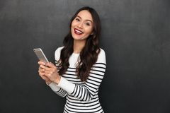 Cheerful Brunette Woman In Sweater Holding Smartphone Stock Photography