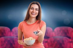 Cheerful brunette woman watching movie. With pop-corn at the cinema Stock Photography