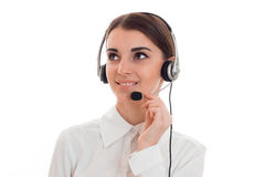 Cheerful brunette woman working in call center with headphones and microphone and smiling aside isolated on white Royalty Free Stock Image