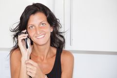 Cheerful brunette young woman at home speak to cell phone, tan beauty girl in house Royalty Free Stock Photo
