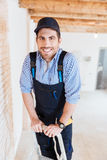 Cheerful builder smiling and standing on the ladder Stock Photo