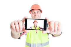 Cheerful builder using phone to take photograph Stock Photo