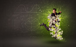 Cheerful businesman jumping with dollar banknotes around him. On background Stock Photo