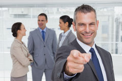 Cheerful businesman pointing at camera with colleagues on backgr. Cheerful businesman in bright office pointing at camera with colleagues on background Stock Image