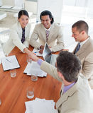 Cheerful Business associates closing a deal. In a meeting stock photo