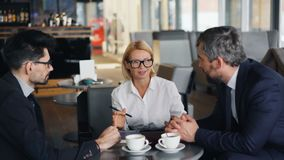 Cheerful business lady negotiating agreement with male partners meeting in cafe