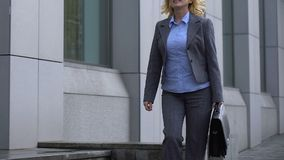 Cheerful business lady with briefcase walking near office building, loving job. Stock footage stock video