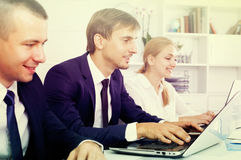 Cheerful business male sitting with coworkers stock image