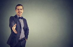 Cheerful business man giving handshake. Smiling stylish young man outstretching hand at camera to give greeting handshake on gray royalty free stock photography