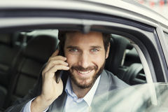 Cheerful business man on mobile phone in rear of the car. Stock Photos