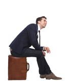 Cheerful business man sitting on suitcase Stock Images