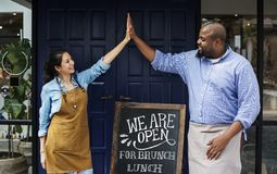 Cheerful business owners standing with open blackboard Royalty Free Stock Photo
