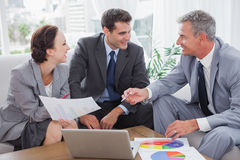 Cheerful business people analyzing financial graphs of their com Royalty Free Stock Photography