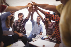 Cheerful business people giving high five while sitting creative office. Group of cheerful business people giving high five while sitting creative office royalty free stock image