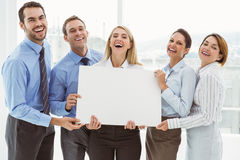 Cheerful business people holding blank board in office Royalty Free Stock Photo