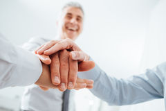 Cheerful business people stacking hands. Cheerful business team stacking hands and smiling, teamwork and success concept, hands close up Stock Photo