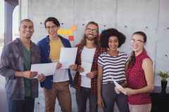 Cheerful business people standing in creative office royalty free stock image