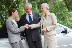 Cheerful business people talking together by classy cabriolet Stock Photos