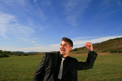 Cheerful business person. Extatic business man with his arm raised Royalty Free Stock Photos