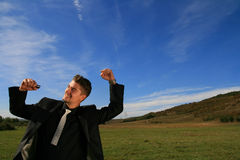 Cheerful business person. Ecstatic business man has his hands raised Stock Photography