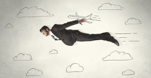 Cheerful business person flying between hand drawn sky clouds Royalty Free Stock Images