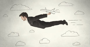 Cheerful business person flying between hand drawn sky clouds Royalty Free Stock Image