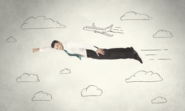 Cheerful business person flying between hand drawn sky clouds. Concept on background Stock Photos