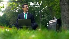 Cheerful business person working on laptop in forest, inspired by nature energy. Stock photo stock image
