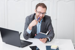 Cheerful business professional looking at meeting schedule notebook royalty free stock images