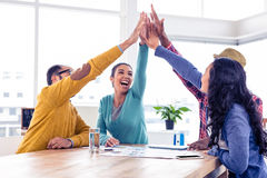 Cheerful business team doing high five in creative office royalty free stock photo