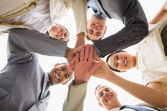 Cheerful business team looking down at the camera with hands together Royalty Free Stock Photography