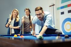Cheerful business team playing billiard after work. Cheerful young business team playing billiard after work Royalty Free Stock Image