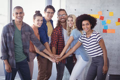 Cheerful business team stacking hands in creative office stock image