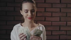 Cheerful business woman counting money for profitable investments in brick studio stock video footage