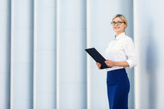 Cheerful business woman holding folder Stock Photo