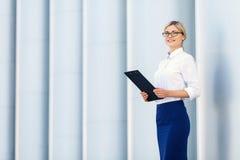 Cheerful business woman holding folder Stock Photo