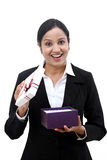 Cheerful business woman holding a gift box. Against white Stock Photos