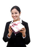 Cheerful business woman holding a gift box. Against white Royalty Free Stock Image