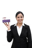 Cheerful business woman holding a gift box. Against white Stock Photography